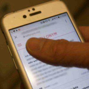 Daumen auf dem Display eines hellen Smartphones